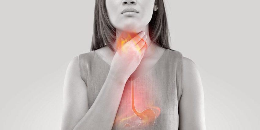 Junge Frau mit Speiseröhrenentzündung hält sich den Hals