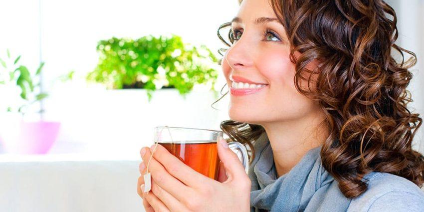Frau trinkt ein Glas Tee und lächelt